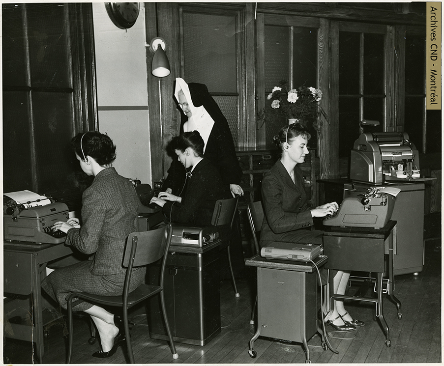 Sister Lucille Goodman supervises the work of the students in the dictaphone lab of Collège de secrétariat Notre-Dame Secretarial College